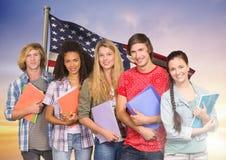Amis avec des livres se tenant contre le drapeau américain à l'arrière-plan Photographie stock libre de droits