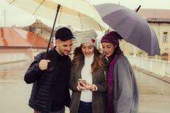 Amis avec des parapluies Photos libres de droits