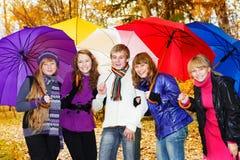 Amis avec des parapluies Photographie stock libre de droits