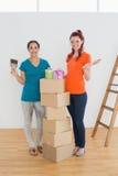 Amis avec des pinceaux, des boîtes et des boîtes dans la nouvelle maison Photos stock