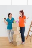 Amis avec des pinceaux, des boîtes et des boîtes dans une nouvelle maison Photo stock