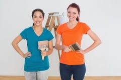 Amis avec des pinceaux et échelle dans une nouvelle maison Image stock
