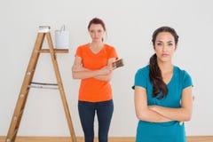 Amis avec des pinceaux et échelle dans une nouvelle maison Photo libre de droits