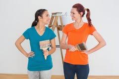 Amis avec des pinceaux et échelle dans une nouvelle maison Photographie stock