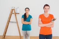 Amis avec des pinceaux et échelle dans une nouvelle maison Image libre de droits