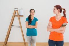 Amis avec des pinceaux et échelle dans une nouvelle maison Images libres de droits