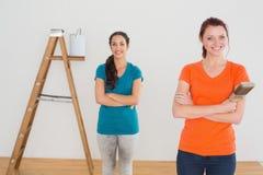 Amis avec des pinceaux et échelle dans une nouvelle maison Photographie stock libre de droits
