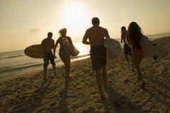 Amis avec des planches de surf fonctionnant vers l'océan Photos stock
