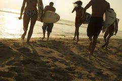 Amis avec des planches de surf fonctionnant vers l'océan Image libre de droits