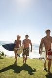 Amis avec des planches de surf marchant à partir de l'océan Images stock