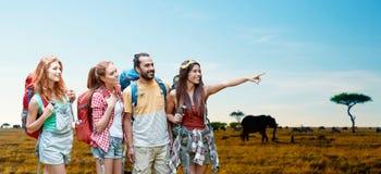 Amis avec des sacs à dos au-dessus de la savane africaine Image libre de droits