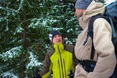 Amis avec des sacs à dos dans la forêt en hiver Photo libre de droits
