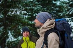 Amis avec des sacs à dos dans la forêt en hiver Photos stock