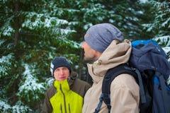 Amis avec des sacs à dos dans la forêt en hiver Images stock