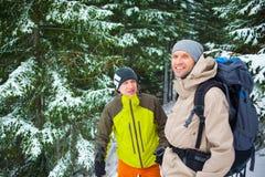 Amis avec des sacs à dos dans la forêt en hiver Photos libres de droits