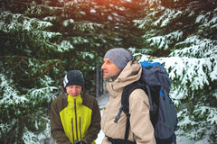 Amis avec des sacs à dos dans la forêt en hiver Photographie stock