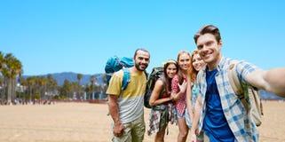 Amis avec des sacs à dos prenant le selfie Image libre de droits