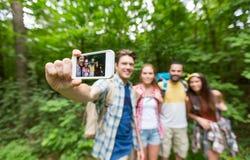 Amis avec des sacs à dos prenant le selfie par le smartphone Photos stock