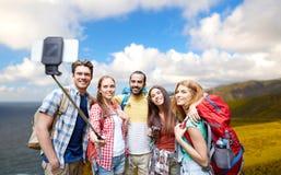 Amis avec des sacs à dos prenant le selfie par le smartphone Images stock