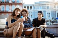 Amis avec des sacs à dos souriant, regardant le téléphone, se reposant près de la vue Photographie stock libre de droits
