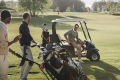 Amis avec des sacs de golf et chariot de golf passant le temps ensemble sur le terrain de golf Photo libre de droits