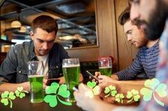 Amis avec des smarphones et bière verte au bar Photo libre de droits