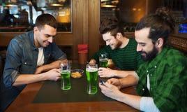 Amis avec des smarphones et bière verte au bar Image libre de droits