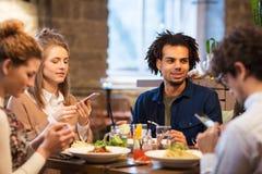 Amis avec des smartphones à la barre ou au restaurant Photographie stock libre de droits
