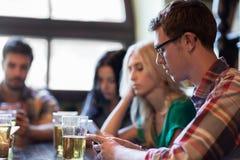 Amis avec des smartphones buvant de la bière et au bar Images stock