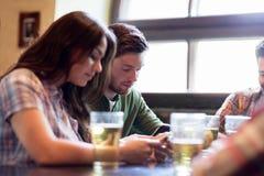 Amis avec des smartphones buvant de la bière et au bar Photos stock