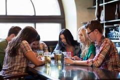 Amis avec des smartphones buvant de la bière et au bar Images libres de droits
