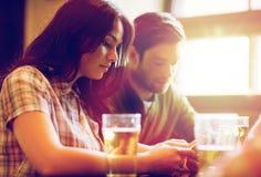 Amis avec des smartphones buvant de la bière et au bar Photographie stock