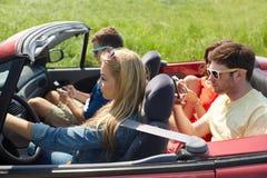 Amis avec des smartphones conduisant dans la voiture de cabriolet Image libre de droits