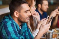 Amis avec des smartphones dinant au restaurant Photos stock