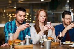 Amis avec des smartphones dinant au restaurant Photo libre de droits