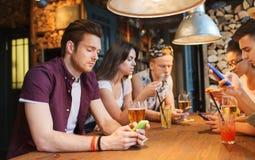 Amis avec des smartphones et boissons à la barre Photo stock
