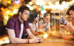 Amis avec des smartphones et boissons à la barre Images libres de droits