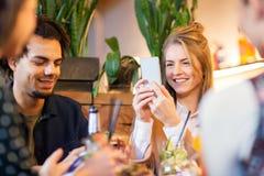 Amis avec des smartphones mangeant au restaurant Photo libre de droits