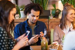 Amis avec des smartphones mangeant au restaurant Image stock