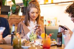 Amis avec des smartphones mangeant au restaurant Images stock