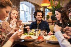 Amis avec des smartphones mangeant au restaurant Photos stock