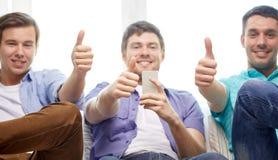 Amis avec des smartphones montrant des pouces  Photographie stock libre de droits