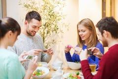Amis avec des smartphones prenant la photo de la nourriture Photographie stock libre de droits
