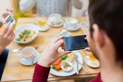 Amis avec des smartphones prenant la photo de la nourriture Photo libre de droits