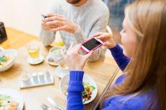 Amis avec des smartphones prenant la photo de la nourriture Photos libres de droits