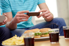 Amis avec des smartphones prenant la photo de la nourriture Photographie stock