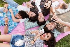 Amis avec des smartphones sur la couverture de pique-nique Photographie stock libre de droits
