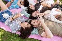 Amis avec des smartphones sur la couverture de pique-nique Photo stock