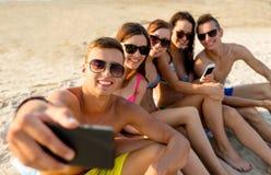 Amis avec des smartphones sur la plage Image libre de droits