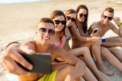 Amis avec des smartphones sur la plage Photo stock